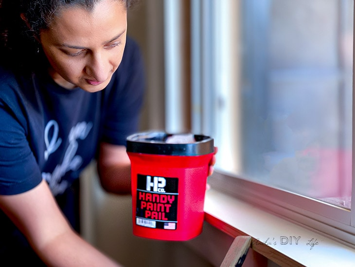 Woman painting trim with handy paint pail
