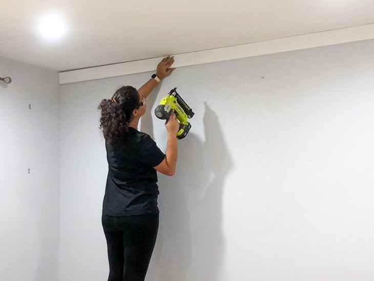 Woman attaching board and batten to wall using nail gun