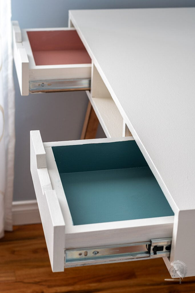 desk with drawers open with pink and turquoise interiors