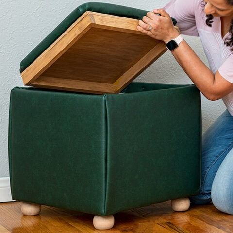 Learn how to build a DIY storage ottoman cube from scratch. The top has a reversible tray. The upholstered ottoman is a super easy build with no sewing involved!