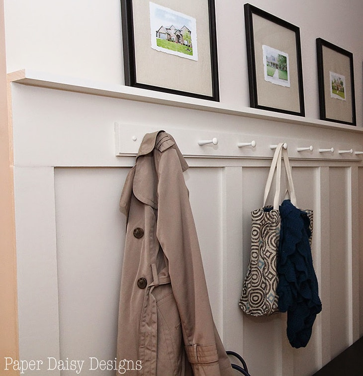Entryway with board and batten with hooks and ledge with pictures