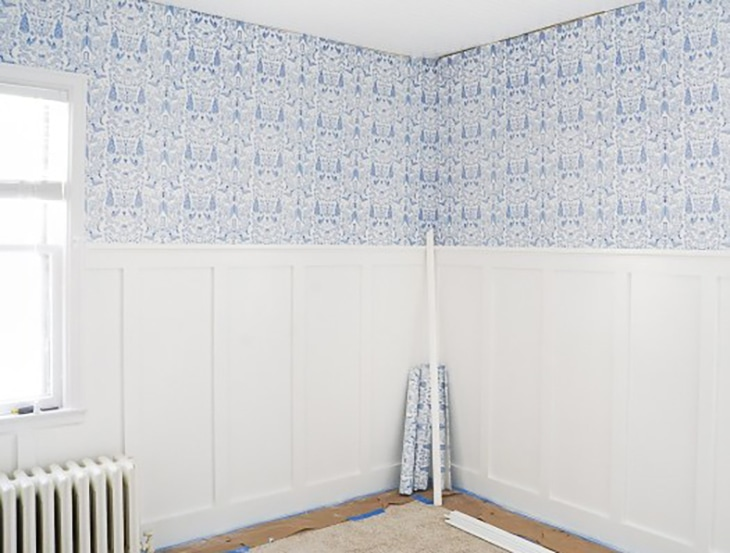 Room with half wall board and batten and wallpaper on top