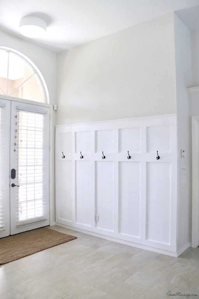 Entryway with white board and batten half wall and hooks
