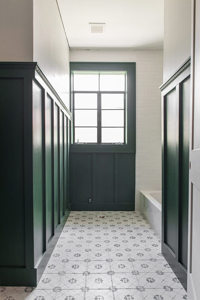 Dark green board and batten wall in a white bathroom with decorative trim detail on top