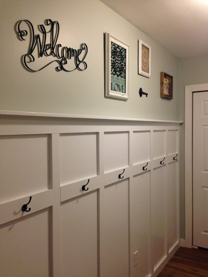 white Entry way board and batten wall with black hooks