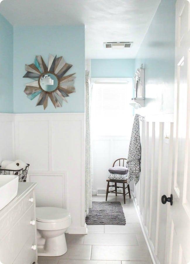 Half wall white board and batten in light blue bathroom