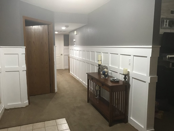 Hallway lined with white board and batten