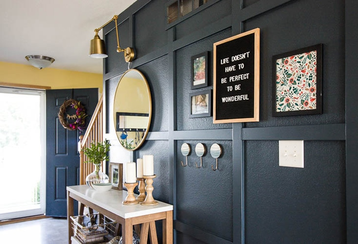 Navy blue board and batten in living room next to stairs