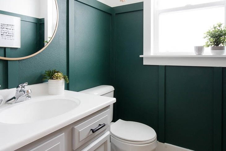Dark green board and batten wall in a white bathroom