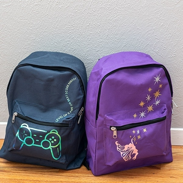 Learn how to make DIY custom backpacks using Iron-on vinyl and Cricut. This is a great way to make special designs and personalize any backpack! We made these to donate to the wonderful cause - Backpacks of Love.