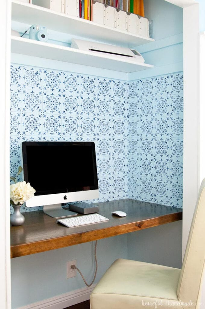 Floating desk in a closet with open shelving above