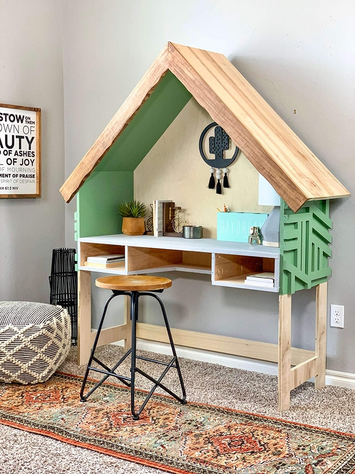 House shaped desk with green accents and two open drawers