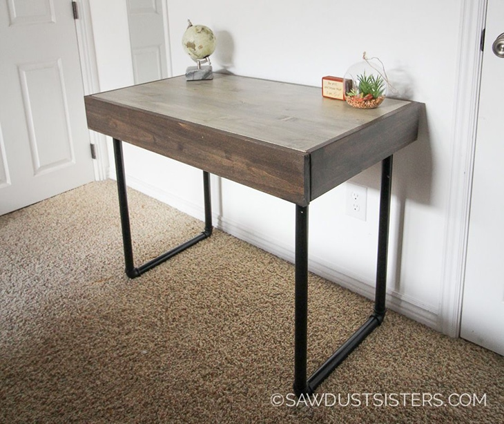 Small wooden desk with black metal pipe legs and hidden drawer