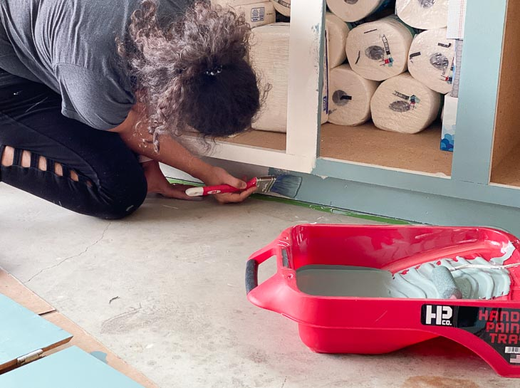 woman painting toe kick of the veneer cabinets