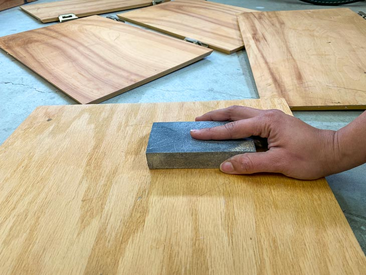 sanding the veneer cabinet with a sanding sponge to prepare for painting