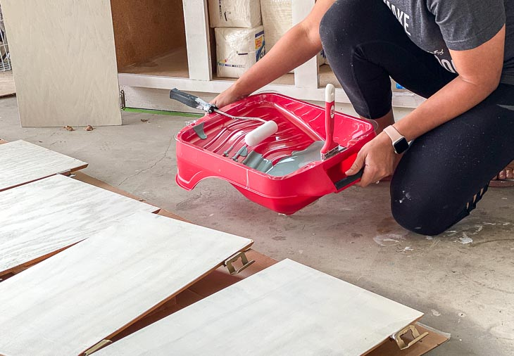 woman holding paint tray with paint for veneer cabinets
