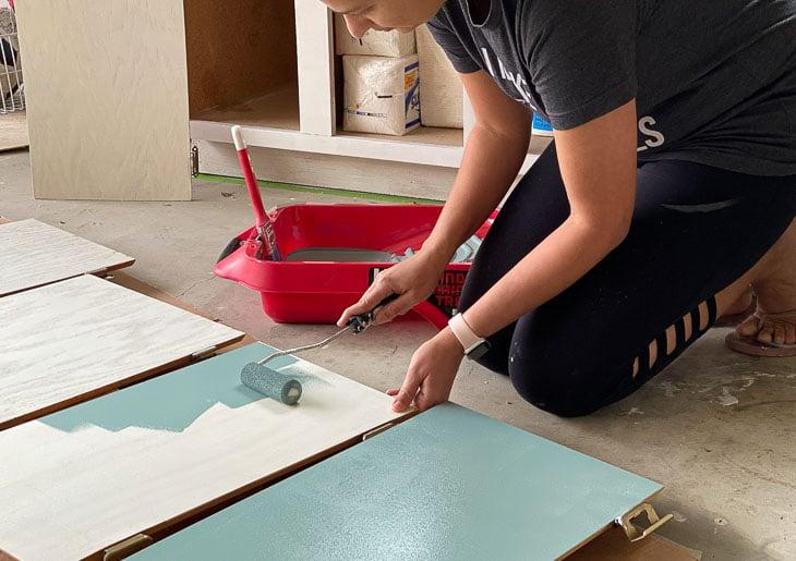 woman painting the veneer cabinet doors