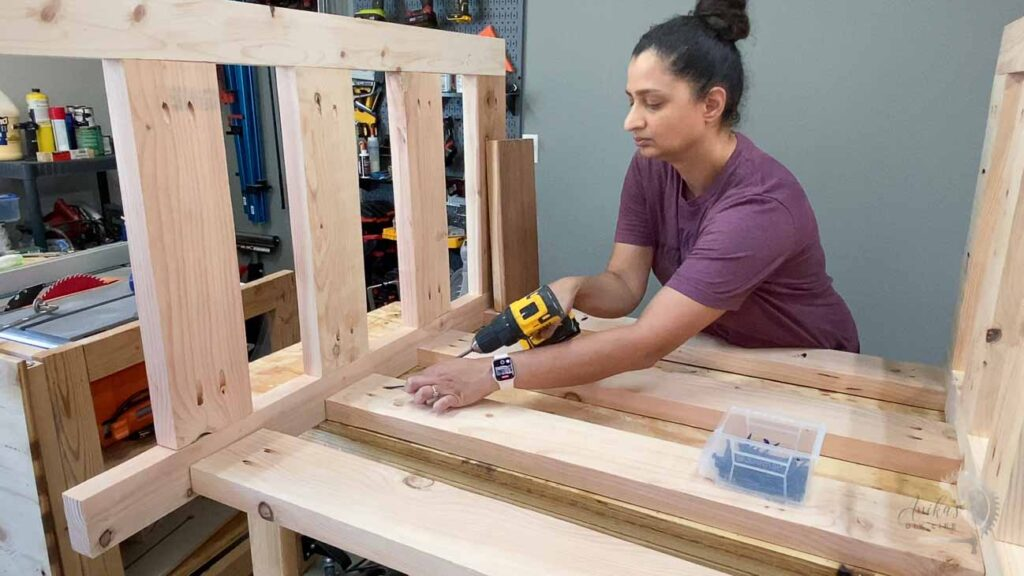 Woman building attaching all the slats to build the leg frame using pocket hole screws