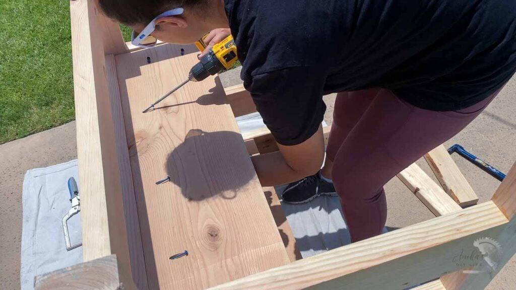 Woman attaching shelf using pocket hole screws