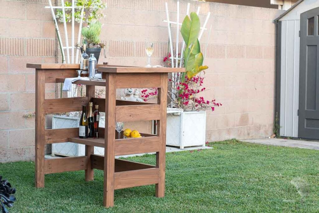 Homemade wooden outdoor bar in backyard with drinks on it