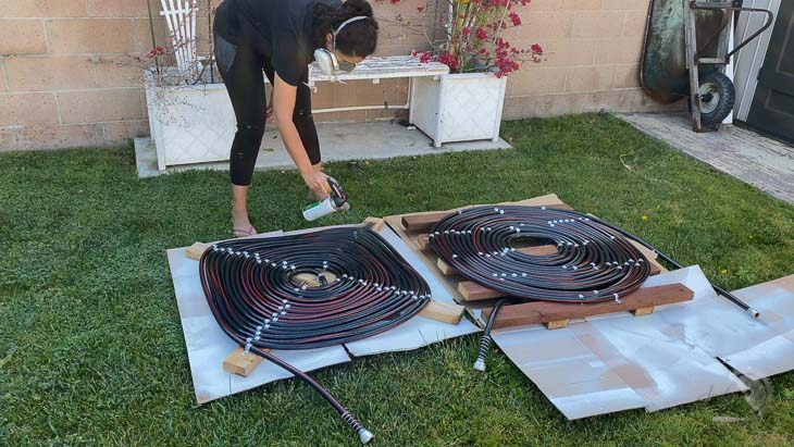 woman spray painting coils black