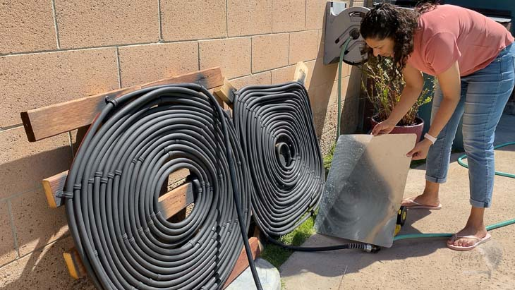 woman adding reflectors tp help solar pool heaters.