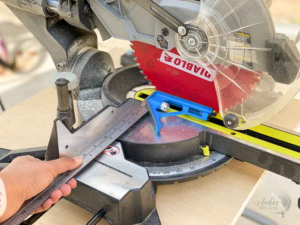 aligning the fence of the miter saw using a combination square to make accurate cuts