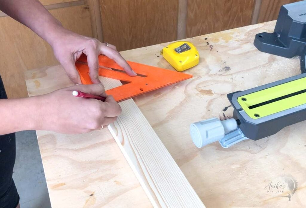 using a speed square to mark the cut line for a miter saw
