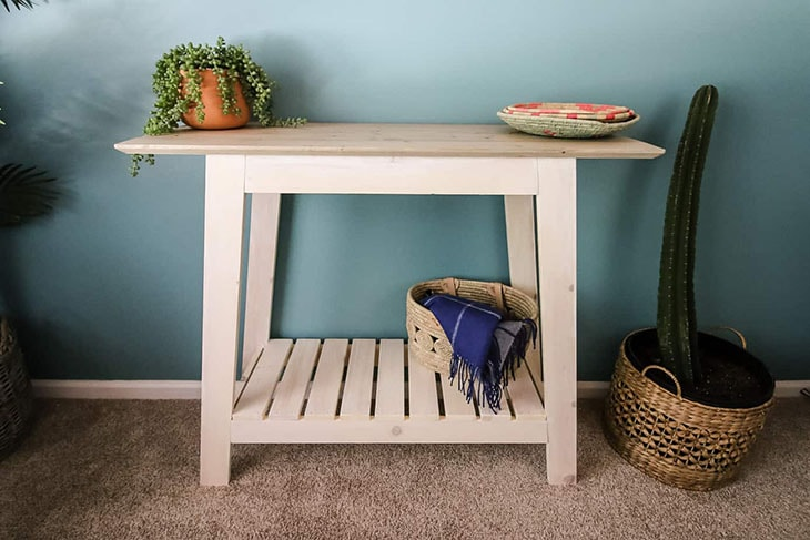 pale pink console table with slatted bottom shelf