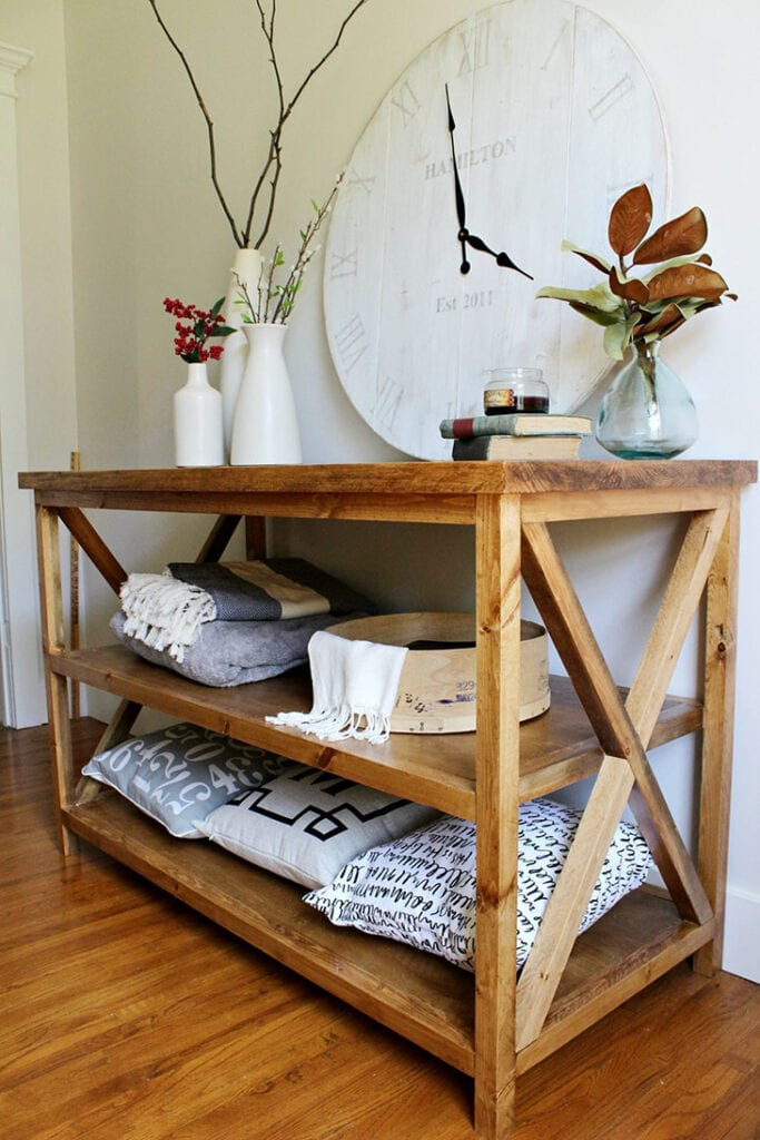 stained wood console table with X details on the sides and two shelves