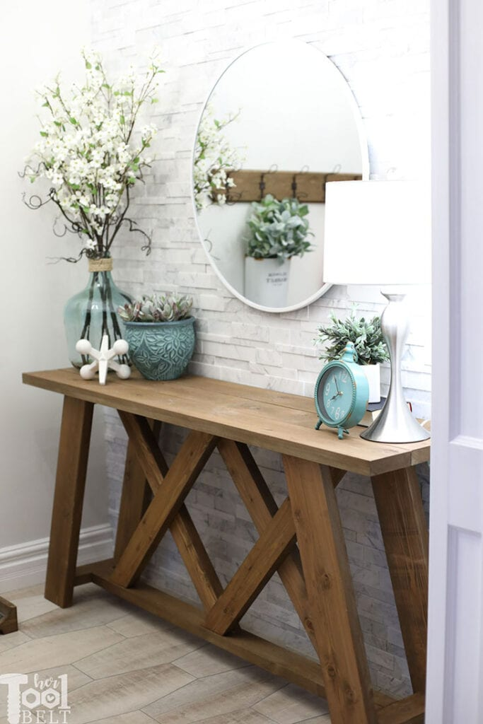 Wooden console table with X design detail against a white tiled wall with mirror above
