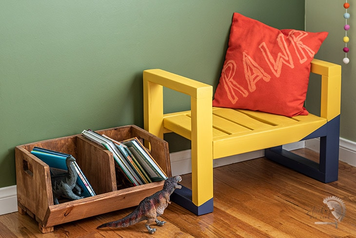 Yellow DIY kids bench in green room with pillow and books.