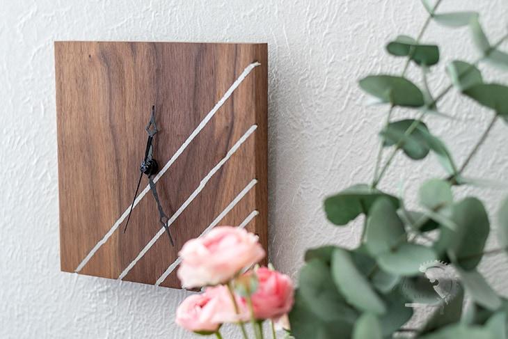 DIY wood wall clock with metal inlay next to pink roses