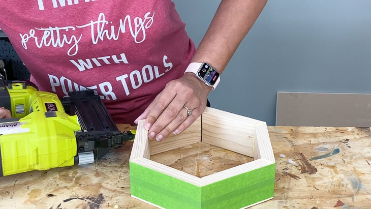 Woman Building a hexagon base  out of wood