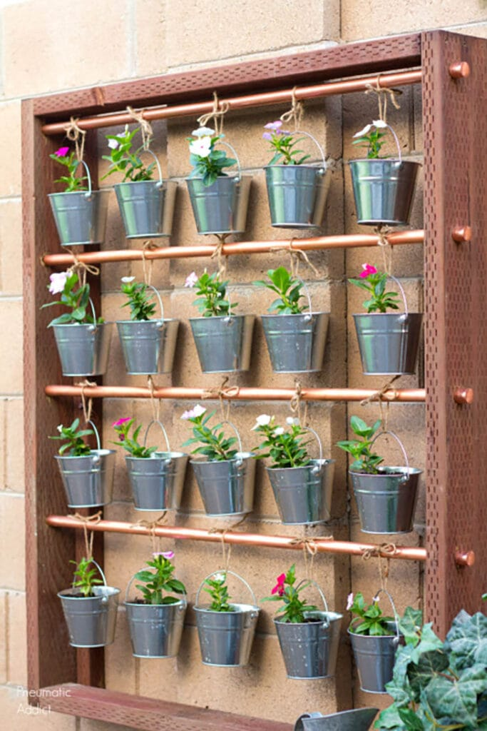 wood and metal hanging garden with twenty small metal buckets with flowers
