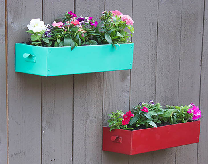 Red and teal metal drawers used as planers on a fence