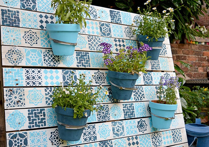 pallet painted with stencil with five flower pots