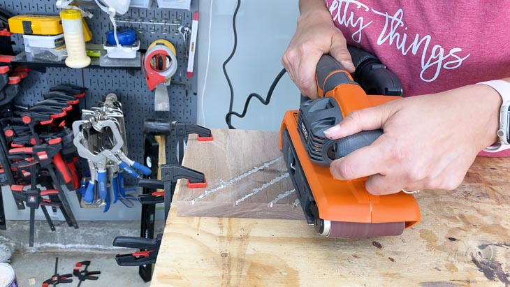 using a belt sander to remove extra metal