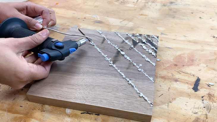 melting solder into grooves of a wood wall clock