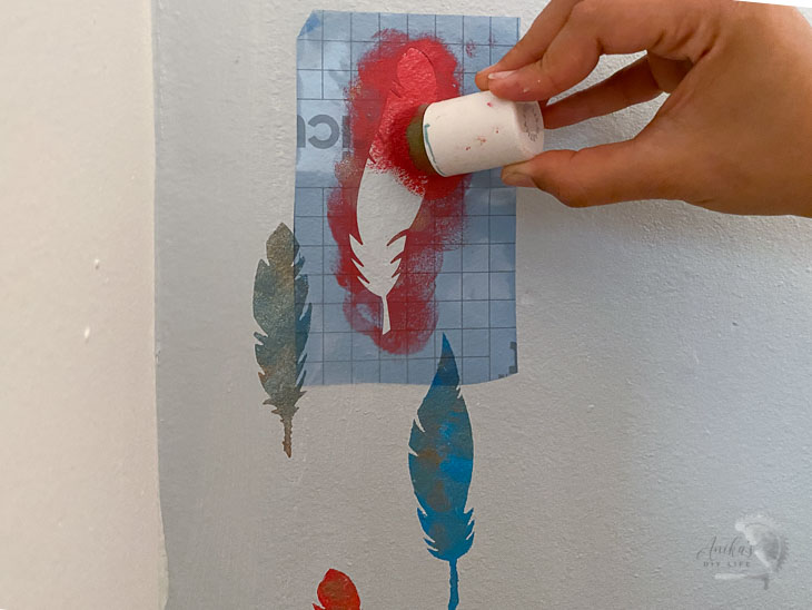 applying red paint to feather stencil on wall