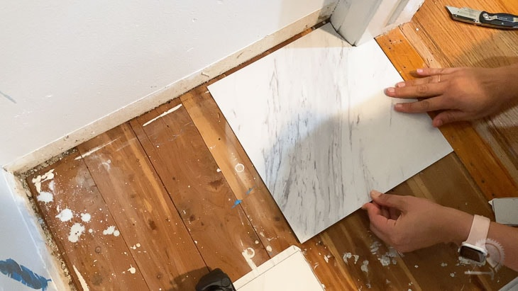 Woman installing peel and stick tile to the closet floor