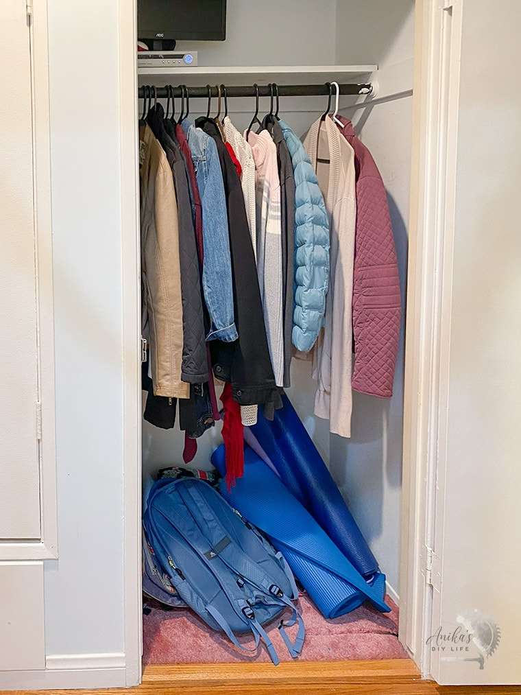 Entryway closet before with coats and pink carpet