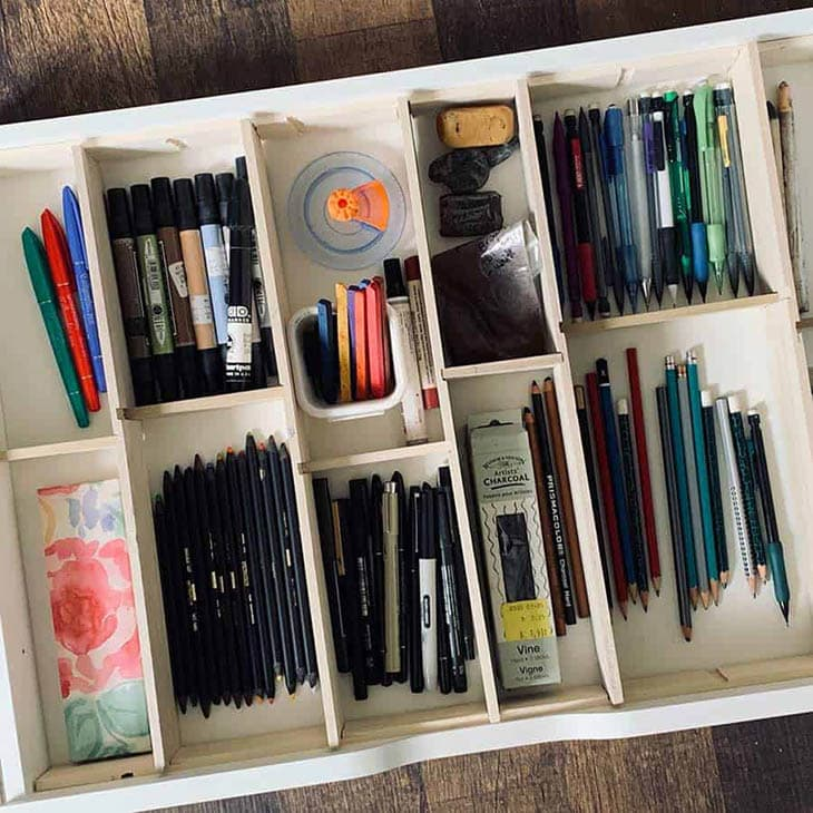 Wooden drawer divider with ten sections filled with office supplies
