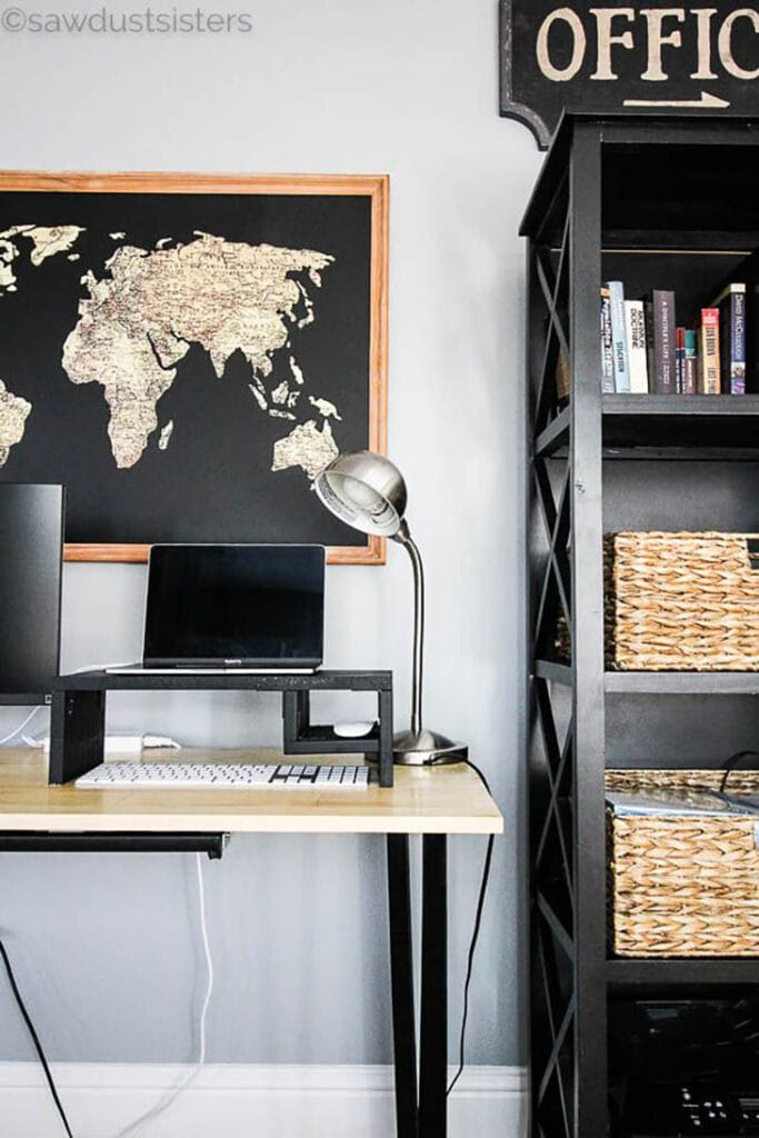 Black painted DIY laptop riser with laptop on it and world map on the wall behind it