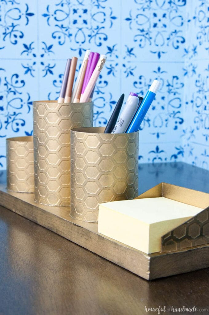 Brass colored pencil holders and post it note holder sitting on a desk
