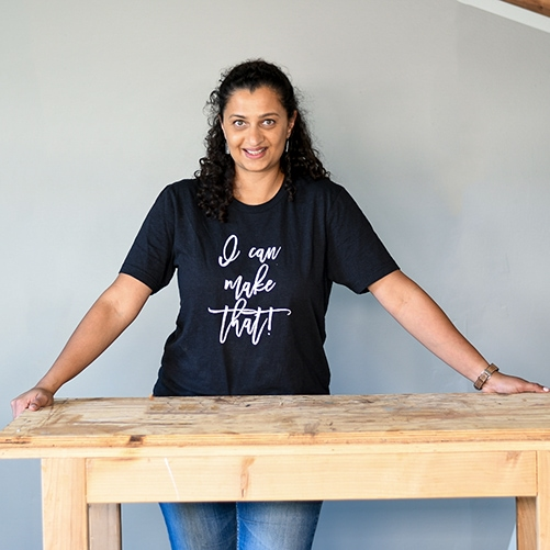 "Woman wearing ""I Can Build That"" T-shirt in workshop"