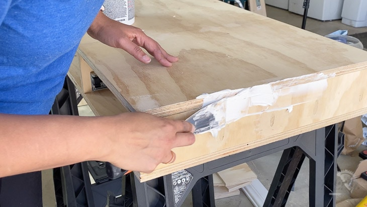 applying joint compound to the plywood to prepare it for painting