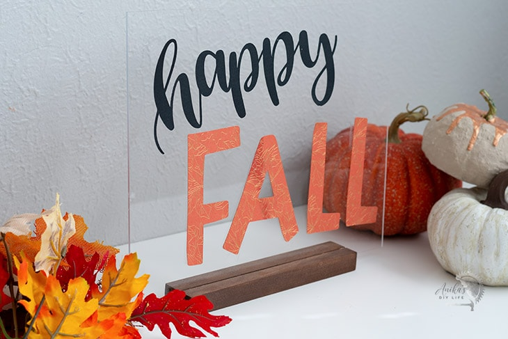 Happy Fall sign on a white table with other fall decorations.