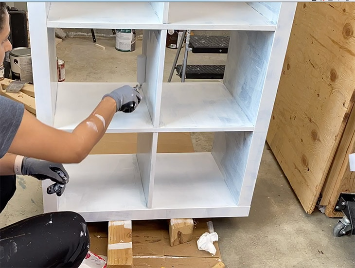 woman applying second coat of primer to laminate ikea furniture