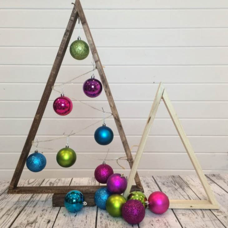 Scrap wood triangles as Christmas trees with colorful ornaments hanging from them